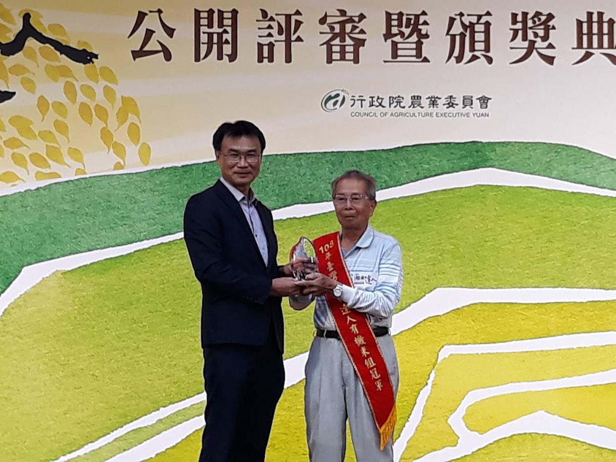 由農委會陳吉仲主任委員頒發謝美國農友「臺灣有機米組」冠軍獎座